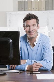 Germany, Munich, business man working in office, smiling, portrait - LDF00636