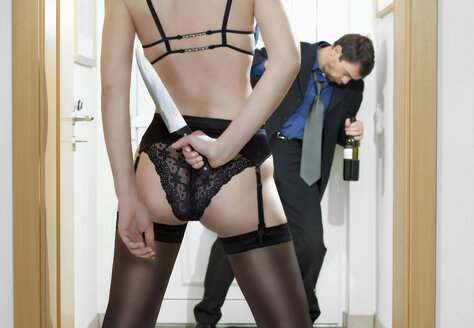 Man coming home, woman waiting with knife, rear view - MAE01682