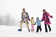 Italy, South Tyrol, Seiseralm, Family holding hands, ice skating - WEST11734