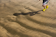 New Zealand, Anaura Bay, Child running across beach, low section - SHF00383