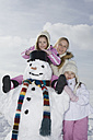 Germany, Bavaria, Munich, Mother and daughters (4-5) (8-9) standing next to snowman, smiling, portrait - RBF00044