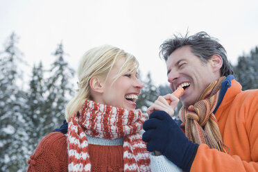 Italy, South Tyrol, Seiseralm, Couple smiling, man holding carrot, smiling, portrait, close-up - WESTF11485