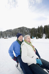 Italy, South Tyrol, Seiseralm,  	 Senior couple sledding down hill, laughing, portrait - WESTF11449