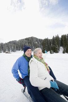Italy, South Tyrol, Seiseralm,   Senior couple sledding down hill, laughing, portrait - WESTF11449