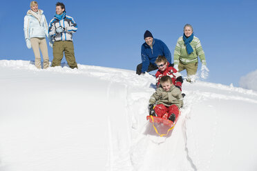 Italy, South Tyrol, Seiseralm, Family sledding - WESTF11416