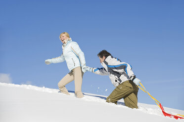 Italy, South Tyrol, Seiseralm, Couple walking in snow, pulling sledge - WESTF11410