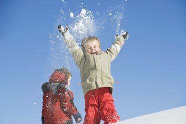 Italy, South Tyrol, Seiseralm, Children throwing snow in the air - WESTF11407