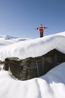 Italy, South Tyrol, Seiseralm, Boy (4-5) standing on snow-covered roof of log cabin - WESTF11398