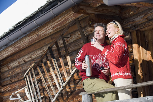 Italy, South Tyrol, Seiseralm, Couple standing on deck of log cabin, holding thermos flask - WESTF11356
