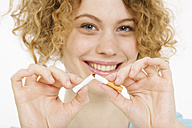 Young Woman breaking cigarette in half, smiling, portrait - CLF00833