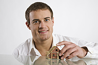 Young man holding model of house, smiling, portrait - RBF00096