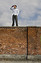 Germany, Bavaria, Munich, Young man on brick wall, watching out - RBF00087