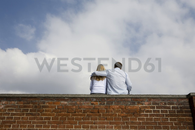 Germany, Bavaria, Munich, Young couple sitting on top of brick wall - RBF00084