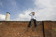 Germany, Bavaria, Munich, Young man sitting on top of brick wall - RBF00081
