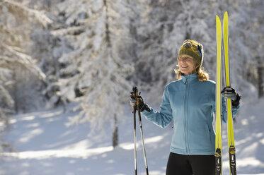 Austria,Tyrol, Seefeld, Wildmoosalm, Woman holding cross-country skis - MIRF00008