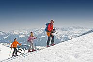Austria, Salzburger Land, Altenmarkt, Zauchensee, Three persons cross country skiing in mountains, side view - HHF02973
