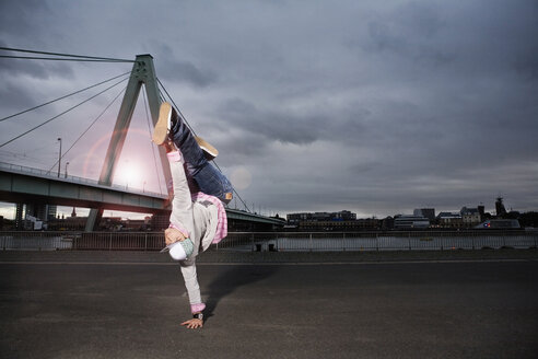 Germany, Cologne, Young man performing breakdance, Rhine bridge in background - SK00011