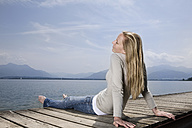 Germany, Chiemsee, Woman sitting on jetty, eyes closed - RBF00106