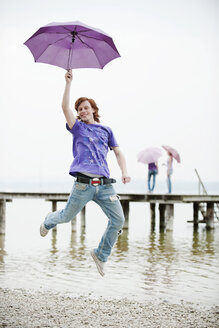 Germany, Bavaria, Ammersee, Young man holding umbrella and jumping - WESTF12251