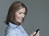 Woman holding mobile phone, looking down, portrait - WEST12269