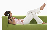 Young woman on sofa wearing headphones, side view - WWF00900