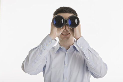 Businessman using binoculars, portrait - LDF00720