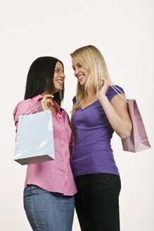 Two women holding shopping bags, laughing, side view, portrait - LDF00751