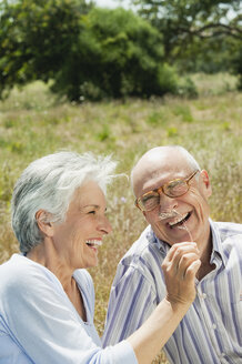 Spain, Mallorca, Senior couple sitting on grass, having fun, portrait - WESTF12939