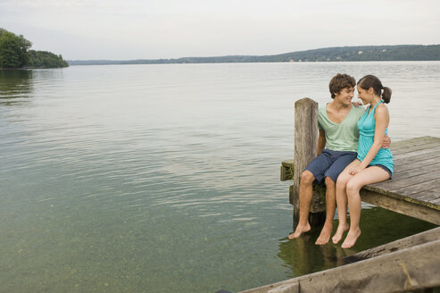Germany, Bavaria, Starnberger See, Young couple sitting on jetty - RNF00068
