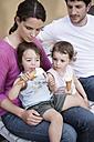 Germany, Berlin, Family sitting on bench, children (3-4) eating icecream, portrait - WESTF13606