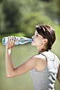 Germany, Bavaria, Young woman drinking water, side view, portrait - MAEF01885