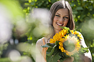 Germany, Bavaria, Woman holding bunch of sunflowers, smiling, portrait - WESTF13249