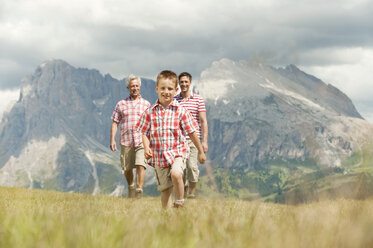 Italy, Seiseralm, Grandfather, Father and son (6-7) walking in meadow, smiling, portrait - WESTF13395