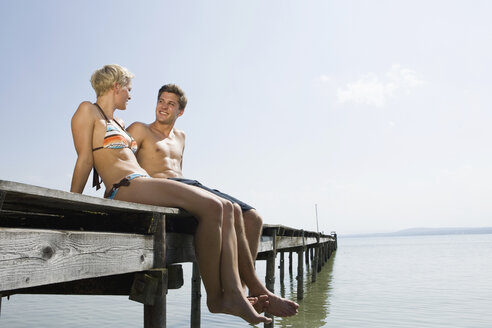 Germany, Bavaria, Ammersee, Young couple relaxing on jetty - LDF00778
