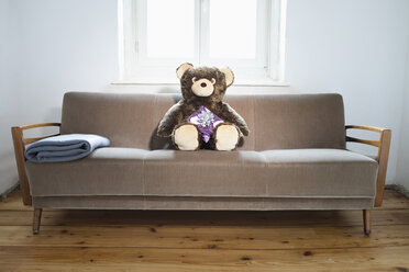 Teddy on sofa with gift parcel - JRF00125