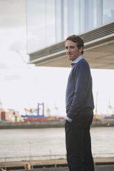 Germany, Hamburg, Businessman standing near quai, portrait - WESTF13846