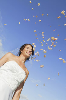 Germany, Bavaria, Bride smiling under falling petals, portrait, low angle view - NHF01180