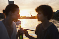 Germany, Berlin, Young couple on boat, holding bottles, side view, portrait - VVF00102