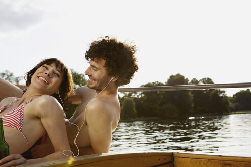 Germany, Berlin, Young couple on motor boat, man wearing headphones, portrait, close-up - VVF00072