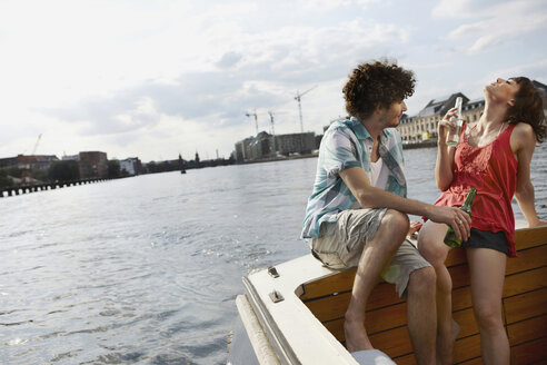 Germany, Berlin, Young couple on motor boat holding bottles, portrait - VVF00063