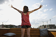 Germany, Berlin, Young woman on motor boat, arms outstretched, raar view - VVF00060