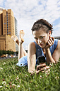 Germany, Berlin, Young woman lying in meadow using mobile phone, portrait - VVF00033
