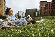 Germany, Berlin, Young couple lying in meadow, high rise buildings in background - VVF00030