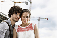 Germany, Berlin, Young couple in front of new building, cranes in background - VVF00021