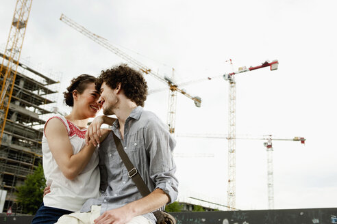 Germany, Berlin, Young couple in front of new building, cranes in background - VVF00015