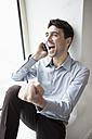 Businessman using mobile phone, rejoicing, portrait - JRF00171