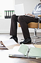 Businessman in office using laptop, documents in foreground, low section - JRF00168