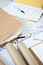 Desk with folder and architectural drawings, close up - JRF00159