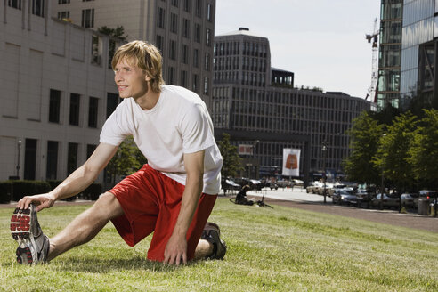 Germany, Berlin, Young man stretching on lawn - SKF00096