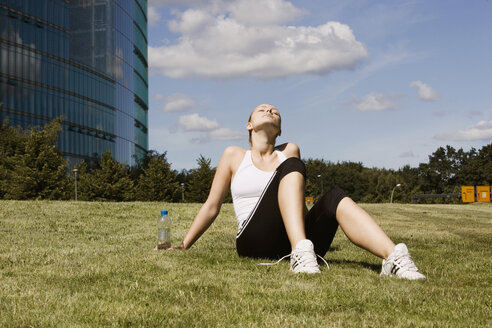 Germany, Berlin, Young woman relaxing on lawn - SKF00084